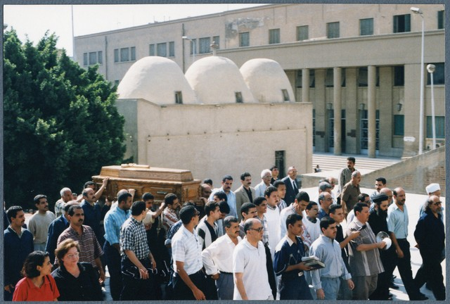 [ Cantor Ibrahim Ayad, holding the cymbals, leads Ragheb Moftah's funeral  procession into St. Mark's Cathedral of Cairo], June 18, 2001