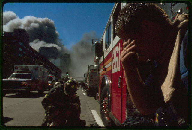 [Fire fighter(?) covering his eyes in foreground with New York City fire fighter, fire trucks, and rescue vehicles on street with burning buildings in background, following September 11th terrorist attack on World Trade Center, New York City]