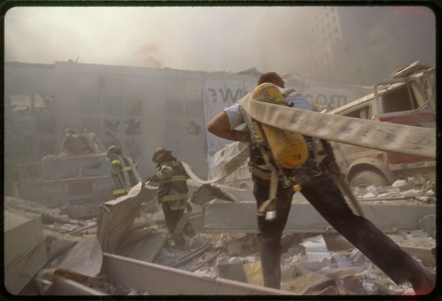 [Fire fighters carrying water hose through rubble September 11th following terrorist attack on World Trade Center, New York City]