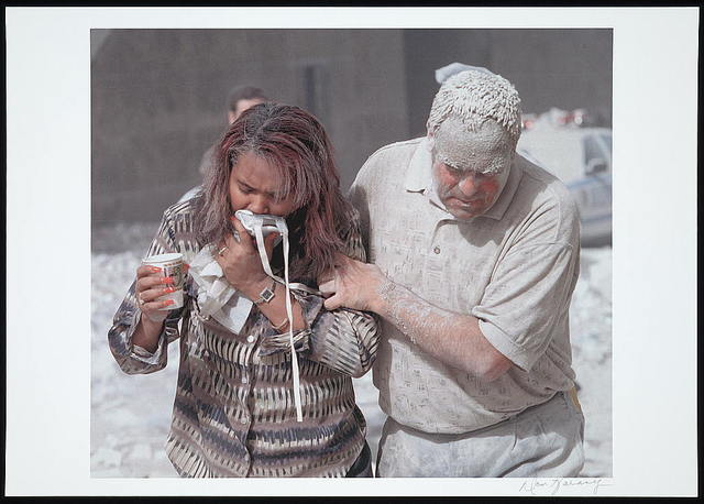[Man covered with ashes assisting a woman walking and holding a particle mask to her face, following the September 11th terrorist attack on the World Trade Center, New York City] / Don Halasy.