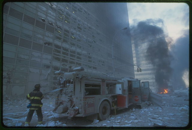 [New York City fire fighter pulling water hose from fire truck amid debris and burning buildings following September 11th terrorist attack on World Trade Center, New York City]