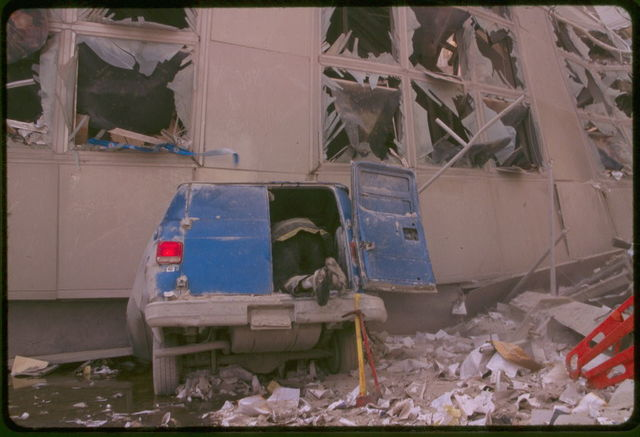[Rescue worker checking inside the back of a van amid debris following September 11th terrorist attack on World Trade Center, New York City]