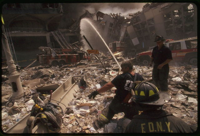 [Three New York City fire fighters spraying water on smoldering ruins following the September 11th terrorist attack on World Trade Center, New York City]