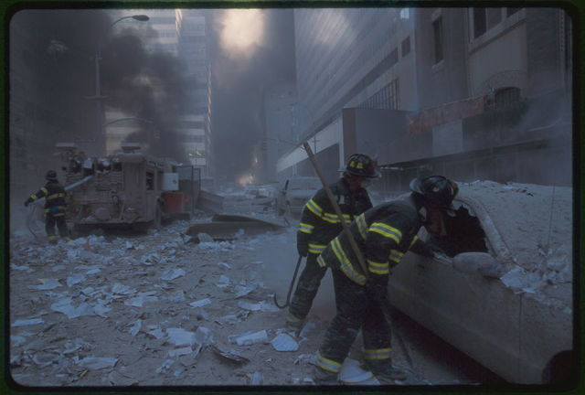 [Two fire fighters looking into car while another New York City fire fighter pulls water hose from fire truck amid smoke and debris following September 11th terrorist attack on World Trade Center, New York City]