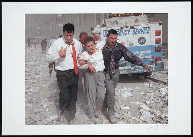 [Two men assisting and walking with an injured woman down a street littered with paper and ashes, following the September 11th terrorist attack on the World Trade Center, New York City] / Don Halasy.