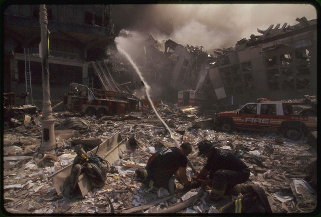 [Two New York City fire fighters spraying water on smoldering ruins following September 11th terrorist attack on World Trade Center, New York City]