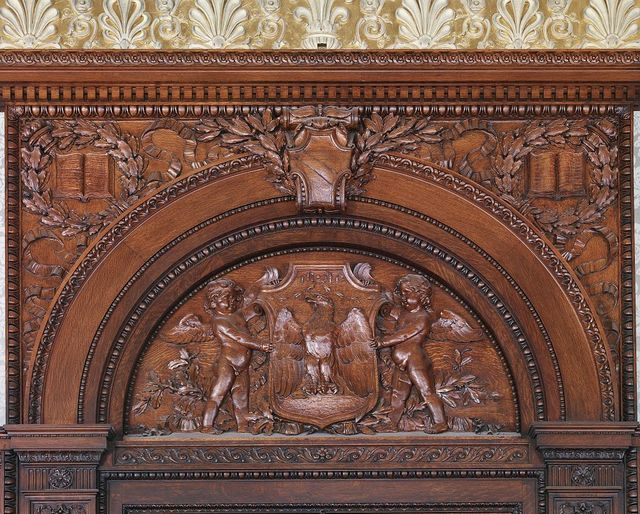 [House Members Room. Oak tympanum above door by Charles H. Niehaus showing a cartouche bearing an eagle supported on either side by cherubs. Library of Congress Thomas Jefferson Building, Washington, D.C.]