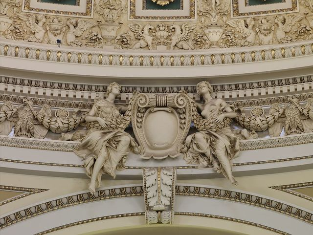 [Main Reading Room. Detail of sculpture showing a cartouche supported by two seated female figures just below the dome. Library of Congress Thomas Jefferson Building, Washington, D.C.]