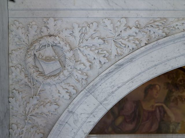 [Second Floor, East Corridor. Detail of spandrel showing carved wreath surrounding a book with lamp. Library of Congress Thomas Jefferson Building, Washington, D.C.]