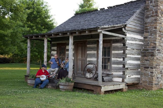 Banjo player Kevin Harris with the Huntley Sisters Blue Grass Group, Larry McWilliams on the fiddle and Nancy Muse on the guitar pose at the one-room log cabin that once served as a stagecoach stop in Tuscumbia, Alabama
