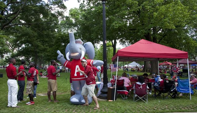 Cody Hahn poses with a blow up of Big Al, the Crimson Tide mascot. Tail gait parties are all over the lawn at the University of Alabama A-Game scrimmage, Tuscaloosa, Alabama