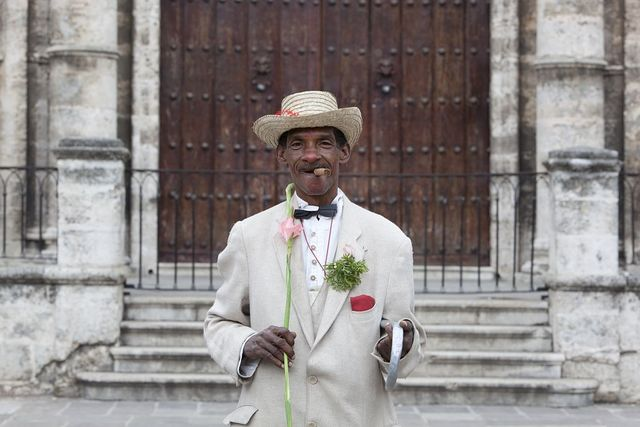 Cubans dress up and pose for the tourist camera like this man smoking a cigar on the Plaza de la Cathedral Square in Havana, Cuba