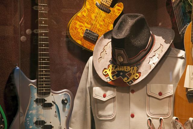 Display of guitars and clothing related to Alabama, a Grammy Award-winning country music and southern rock band that originated in Fort Payne, Alabama