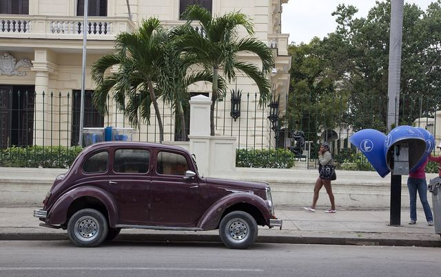 Vintage car and telephone pods in Havana, Cuba