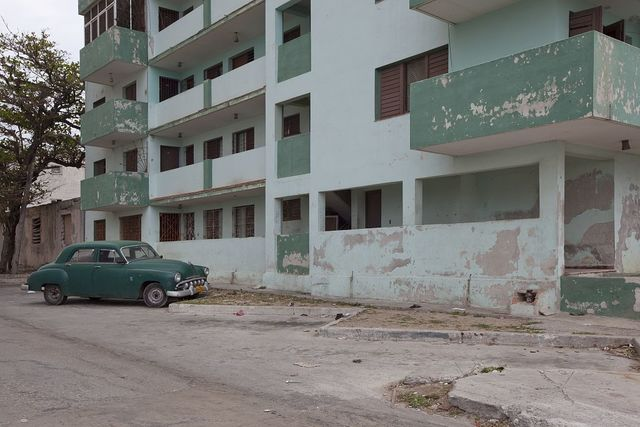 Vintage car matches the color of the building off the Malecón in Havana, Cuba