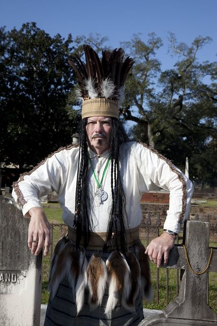 Wayne Dean, dressed as Joe Cain, Jr., poses at the grave of Joseph Stillwell Cain, Jr., in the Church Street Cemetery in Mobile, Alabama