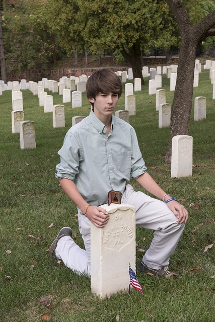 """Christian Liljenquist poses at the grave of a soldier (""""Nath'l Shoup, Sgt. Pa."""") who died during the Civil War. An ambrotype photo of Shoup is on top of the gravestone. Alexandria National Cemetery, Alexandria, Virginia"""