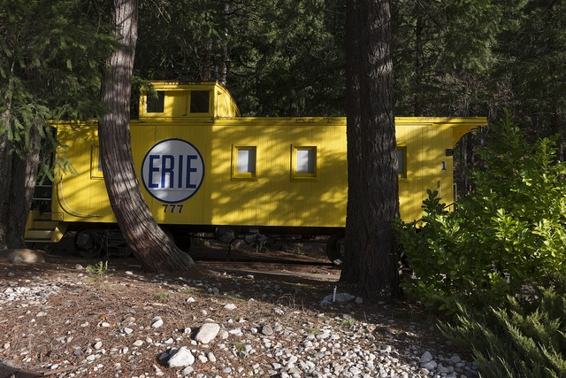A yellow caboose at Rail Road Park, an unusual motel and resort complex in which guests may opt to stay and sleep in a caboose or other restored, antique railroad car. Dunsmuir, California