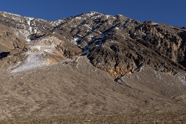 In this fairly rare antithetical view of a parched summer day in Death Valley, December snow has brushed a mountainside above a field  of cacti in that remote California national park