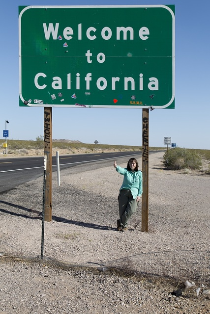 Photographer Carol M. Highsmith and Welcome sign in Mojave Desert, California