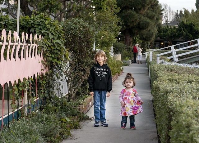 Cousins Sammy Kenyon and Emma Mozenter stroll a pathway next to the famous canals of Venice Beach in the western reaches of Los Angeles, California