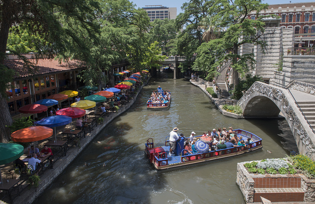 A barge loaded with visitors pass a row of colorful food and beverage purveyors' umbrellas on a portion of the San Antonio River that winds though San Antonio's lively, underground River Walk, which turned an unsightly slum into an international tourist attraction