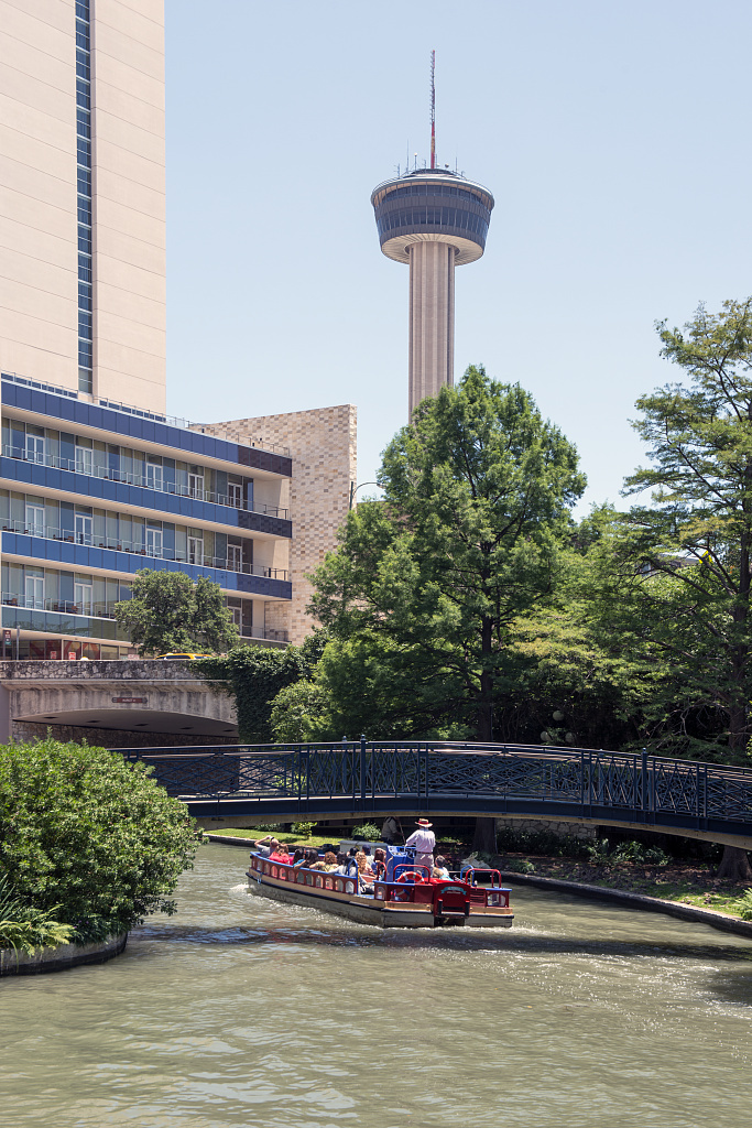"""A barge loaded with visitors plies a portion of the San Antonio River that winds though San Antonio's lively, underground River Walk, which turned an unsightly slum into an international tourist attraction. Looming in the distance on the streets above is the Tower of the Americas, the theme structure of the 1968 """"HemisFair"""" World's Fair"""