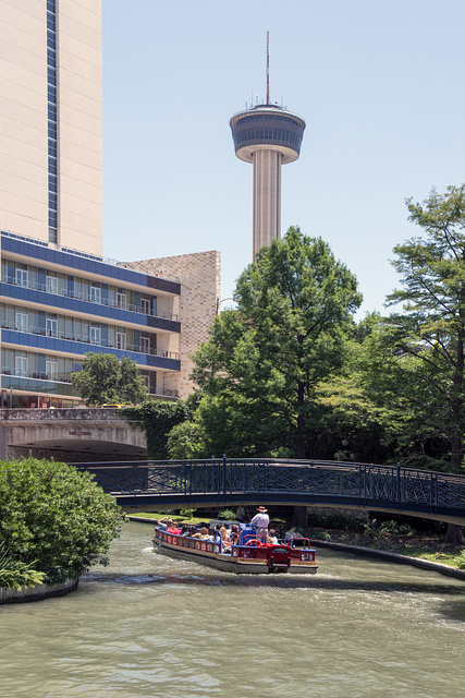 "A barge loaded with visitors plies a portion of the San Antonio River that winds though San Antonio's lively, underground River Walk, which turned an unsightly slum into an international tourist attraction. Looming in the distance on the streets above is the Tower of the Americas, the theme structure of the 1968 ""HemisFair"" World's Fair"