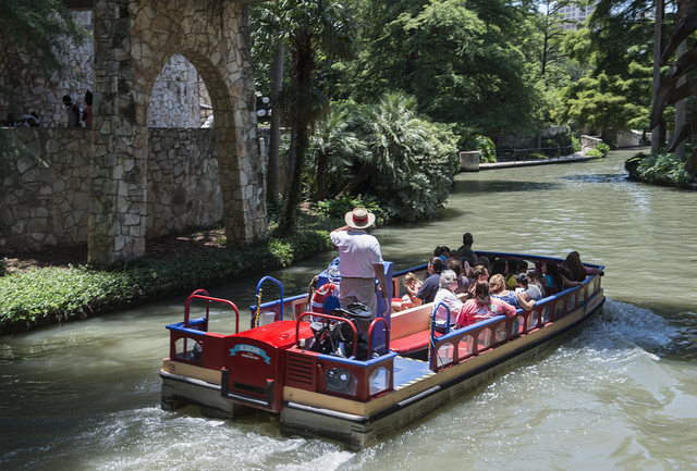 A barge loaded with visitors plies a portion of the San Antonio River that winds though San Antonio's lively, underground River Walk, which turned an unsightly slum into an international tourist attraction