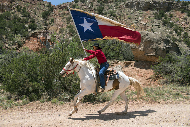 "A highlight of the ""Texas"" outdoor musical drama, staged in the Pioneer Amphitheater carved from the rocks of Palo Duro Canyon southeast of Amarillo in the Texas Panhandle, are majestic rides along the canyon rim by Paul Lundergeen, aboard his white stallion, Ghost. Following his initial gallop, more than 60 performers take the stage to tell the story of the Lone Star State in song and dance"