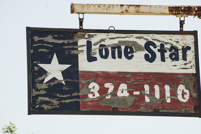"""A tattered advertising sign that borrowed the motif of the Texas state """"lone star"""" flag"""