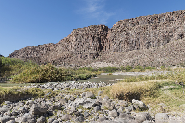 A view of the Rio Grande River, looking generally west, in Big Bend Ranch State Park, Brewster County, Texas. The rock formation to the right is in the United States, the sliver of green to the left in Mexico