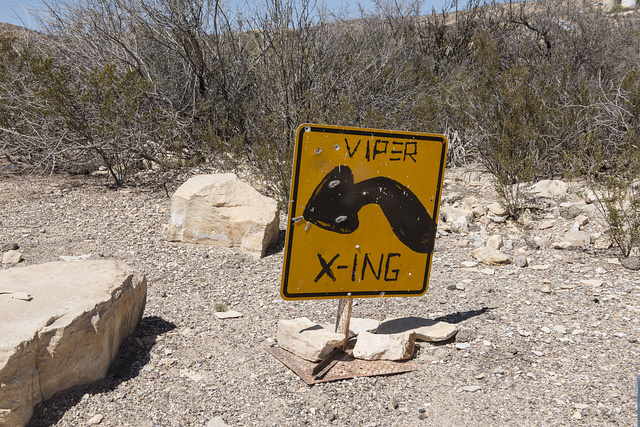 "A whimsical pedestrian-crossing sign in the ""ghost town,"" some of which is still occupied and some of which consists of ruins of the Chisos quicksilver-mining company which operated from 1905 into the early 1940s, and the residences of those who worked there. Terlingua, Texas"
