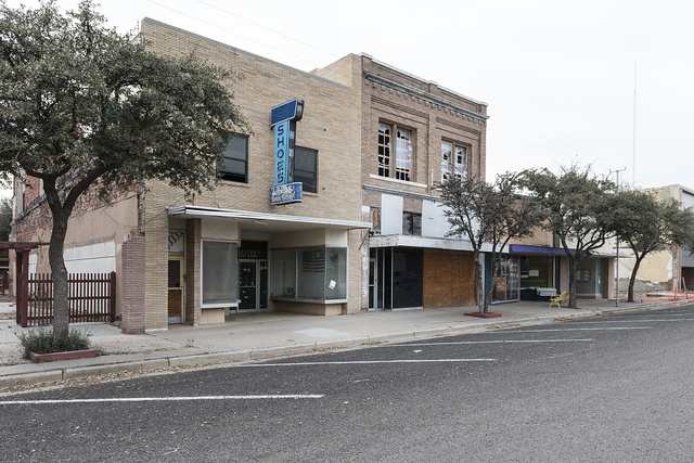 An abandoned shoestore and adjacent structures in Pecos, the seat of Reeves County, Texas