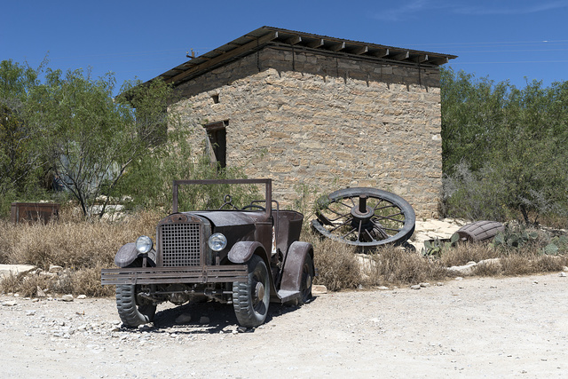 "An old jalopy outside an abandoned stone building in the ""ghost town,"" some of which is still occupied and some of which consists of ruins of the Chisos quicksilver-mining company which operated from 1905 into the early 1940s, and the residences of those who worked there. Terlingua, Texas"
