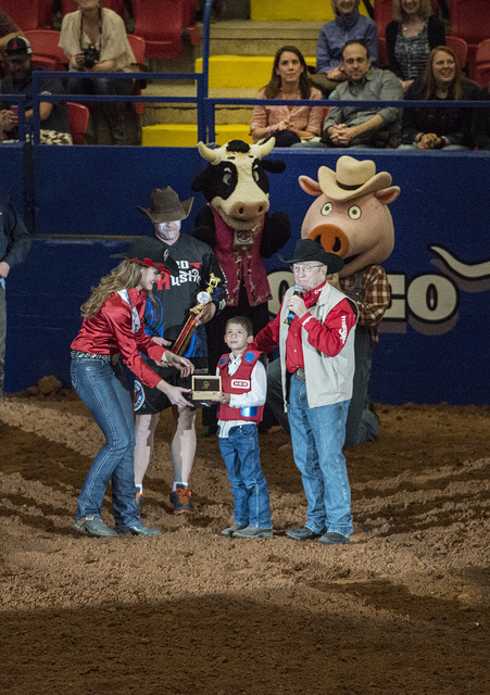 Boy receives an award from the rodeo queen as mascots look on at Rodeo Austin, the city's annual stock show and rodeo. Austin, Texas