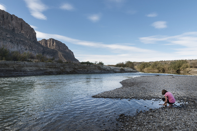 Child gathers stones at the shoreline of the Rio Grande River in Big Bend National Park, Texas
