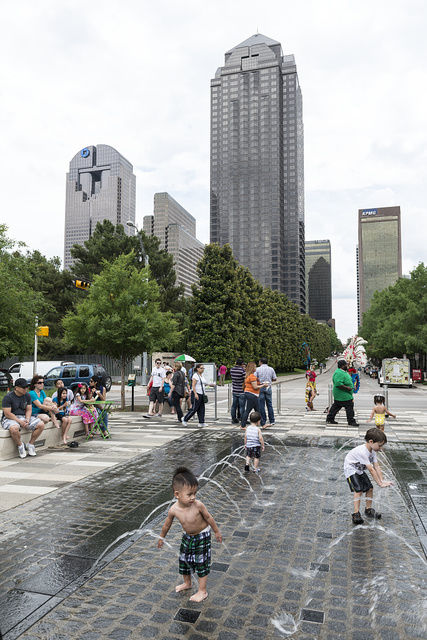 Children enjoy a splash in a decorative pool in Klyde Warren Park, completed in 2012 in the arts district of Dallas, Texas
