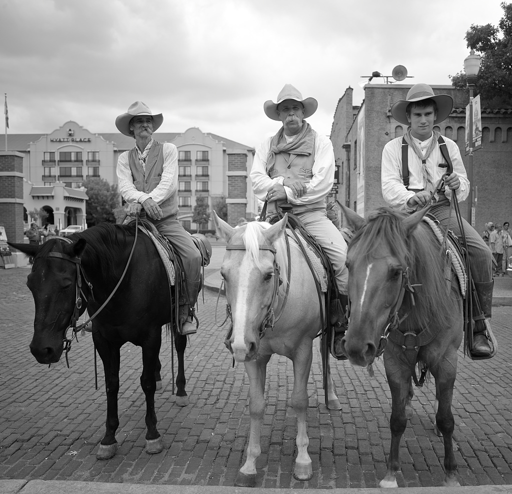 """Cowpokes Mike Maltby, David Mangold, Lane Hopper, left to right on horseback, who help herd Texas Longhorn cattle during a twice-daily stroll (as opposed to any """"running of the bulls"""") in the Stockyards Station neighborhood of Fort Worth, Texas"""