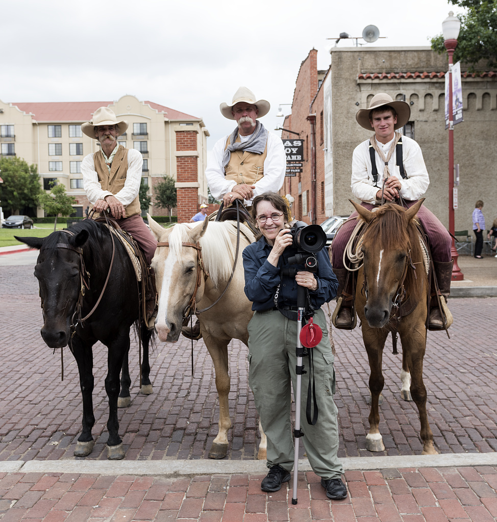 """Cowpokes Mike Maltby, David Mangold, Lane Hopper, left to right on horseback, who help herd Texas Longhorn cattle during a twice-daily stroll (as opposed to any """"running of the bulls"""") in the Stockyards Station neighborhood of Fort Worth, Texas, join photographer Carol M. Highsmith for a photo."""