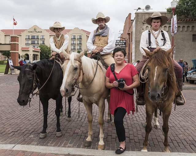 """Cowpokes Mike Maltby, David Mangold, Lane Hopper, left to right on horseback, who help herd Texas Longhorn cattle during a twice-daily stroll (as opposed to any """"running of the bulls"""") in the Stockyards Station neighborhood of Fort Worth, Texas, join Lola Lavender-Hardisty, the Stockyards' official photographer, for a photo"""