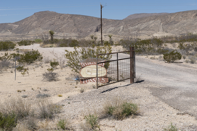 "Dilapidated sign and gate announcing ""Badlands Fossils"" stand along the road that connects Big Bend National Park with its state equivalent, Big Bend Ranch State Park, in southern Brewster County, Texas"