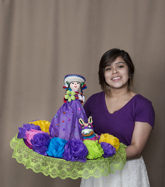 """Elexis Bermejo a student at the the Academy of Careers and Technologies Charter School in San Antonio, Texas, holds her creation exhibited in the """"Hats Off to Fiesta!"""" event, sponsored by the University of Texas at San Antonio's Institute of Texan Cultures, as part of the month-long Fiesta San Antonio celebration"""