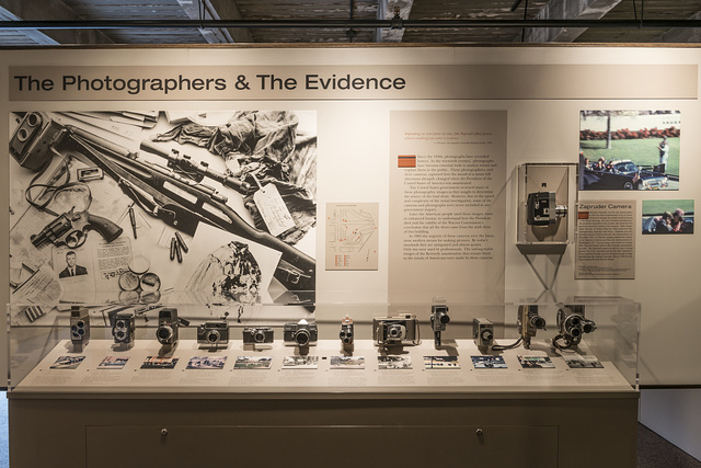 Exhibit showing cameras used by those who watched in horror as President John F. Kennedy, passing them by along Dealey Plaza in Dallas, Texas, was shot and killed by an assassin or assassins' bullets on Nov. 22, 1963. The camera in the case to the right is not the original but an exact copy of the famous 8 mm Bell & Howell Zoomatic film camera used by Abraham Zapruder, a Dallas clothing manufacturer who recorded the famous frames of the fatal blows to the president