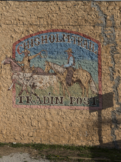 Faded advertising mural for the Chisholm Trail Tradin' Post in Meridian, a town in Bosque County, Texas