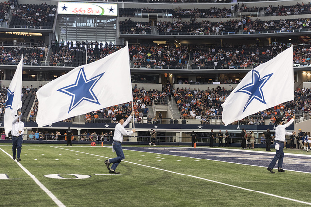 Flag-bearers in cowboy hats whip up enthusiasm in the crowd with a brisk run with flags displaying the Dallas Cowboys' lone-star emblem at the Cowboys' home field AT&T Stadium in Arlington, Texas