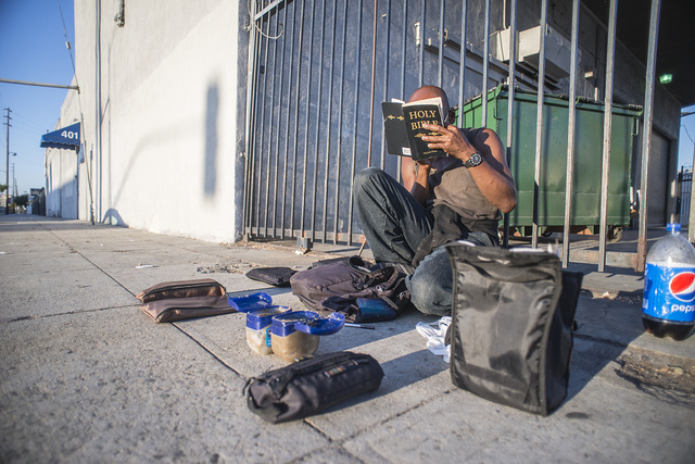 Jeffrey reading aloud from the Apocalypse, S. Central Ave., at 4th St., LA, 2014.  Jeffrey came from Gary, Indiana, and was in the US Navy. He believes that the Bible is in code, it tells how the body works.