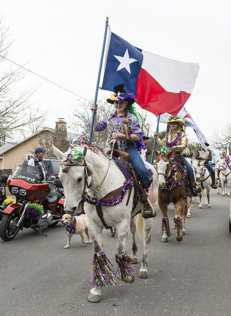 "Jessi Lauppe carries the Texas flag in the annual Mardi Gras parade with a Texas touch in little Bandera, the ""Cowboy Capital of Texas,"" west of San Antonio, Texas"