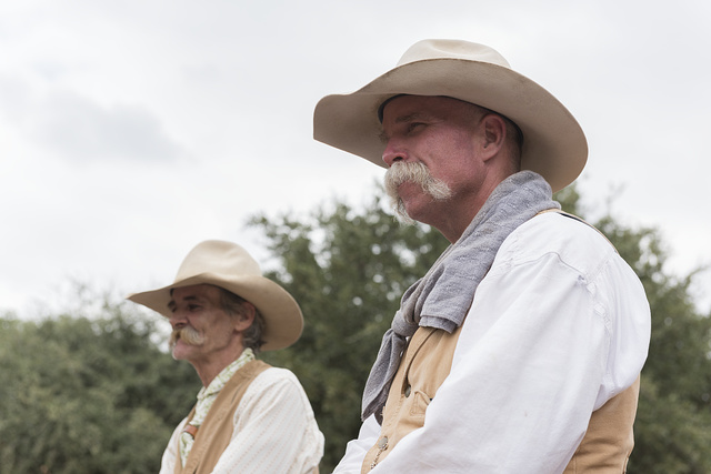 """Mike Maltby and David Mangold, two cowpokes who help herd Texas Longhorn cattle during a twice-daily stroll (as opposed to any """"running of the bulls"""") in the Stockyards Station neighborhood of Fort Worth, Texas"""