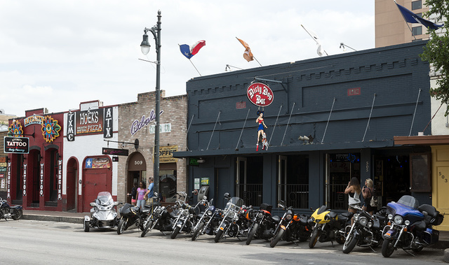 """Motorcycles parked outside the Dirty Dog Bar on East Sixth Street, locally known as """"Dirty Sixth,"""" in Austin, Texas"""